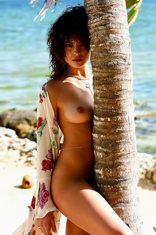 Curly brunette strips at the beach