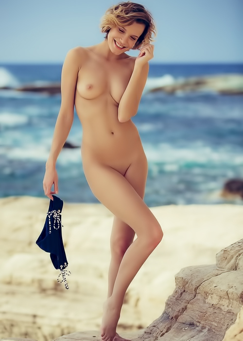 Slim babe poses in the sand