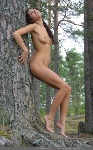 Naked babe poses in forest flowers