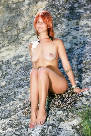 Ginger cutie rubs naked curves high in the mountains
