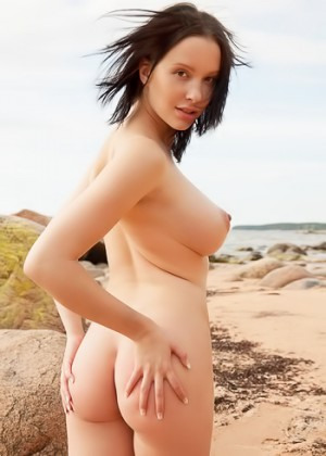 Busty beauty naked at the beach spreads herself in the sand